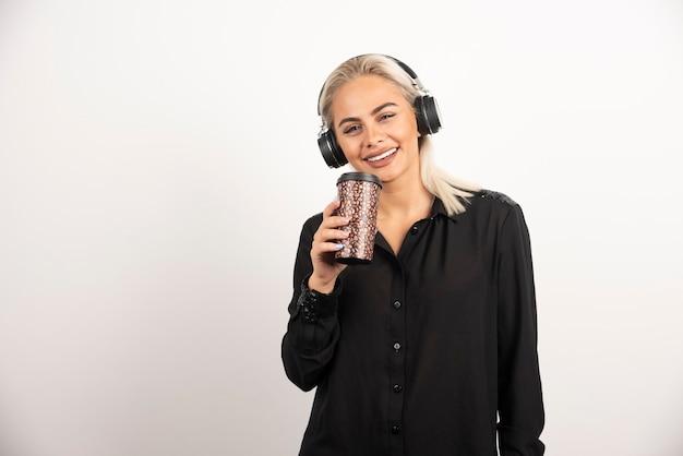 Młoda kobieta z kubkiem w słuchawkach na czerwonym tle. wysokiej jakości zdjęcie