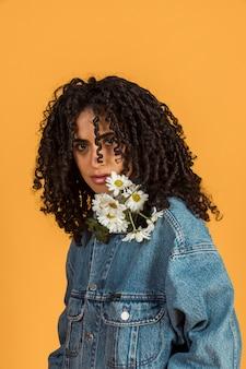 Młoda kobieta z kwiatami przy szyją patrzeje kamerę