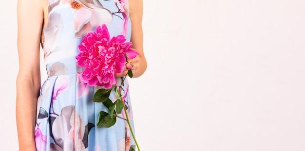 Młoda kobieta z kwiatem piwonii w dłoni na jasnoróżowym tle