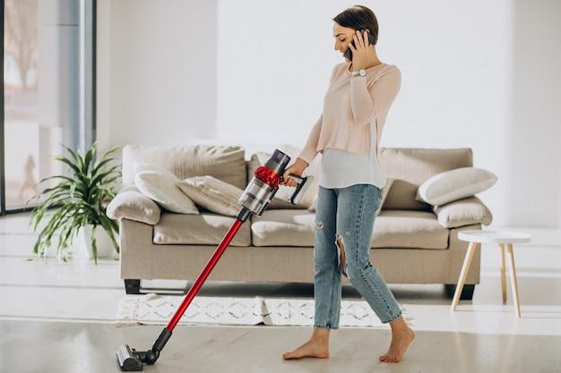 Młoda kobieta z ładowalnym odkurzaczem do czyszczenia w domu