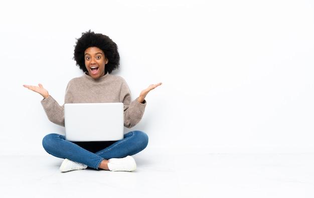 Młoda kobieta z laptopa siedząc na podłodze z zszokowanym wyrazem twarzy