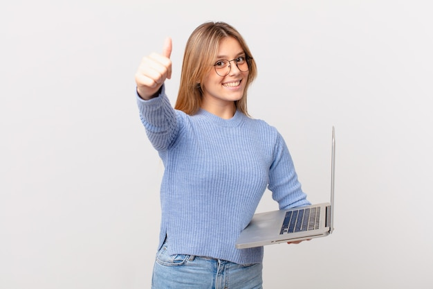 Młoda kobieta z laptopem czuje się dumna, uśmiecha się pozytywnie z kciukami w górę