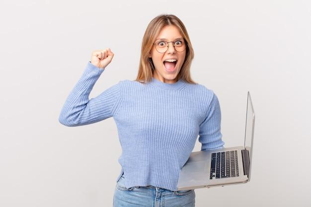 Młoda kobieta z laptopem krzyczy agresywnie z gniewnym wyrazem twarzy