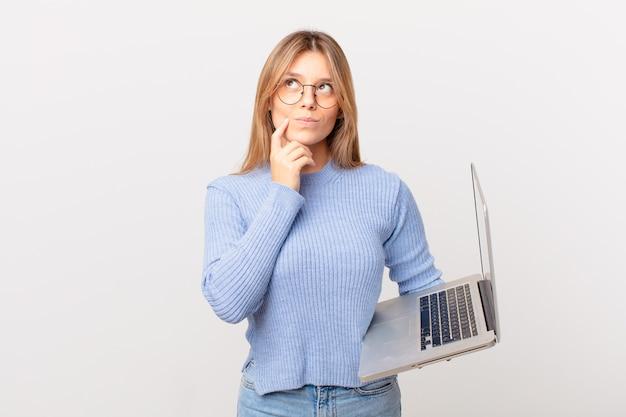 Młoda kobieta z laptopem myśli, wątpi i jest zdezorientowana