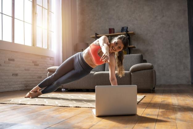 Młoda kobieta z laptopem podąża za ćwiczeniami na siłowni, które są w domu z powodu kwarantanny koronawirusa