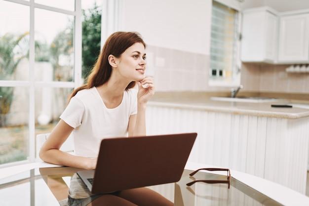 Młoda kobieta z laptopem przy stołem pracuje i odpoczywa