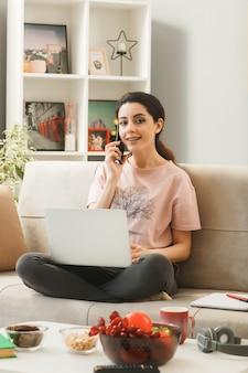 Młoda kobieta z laptopem rozmawia przez telefon, siedząc na kanapie za stolikiem kawowym w salonie