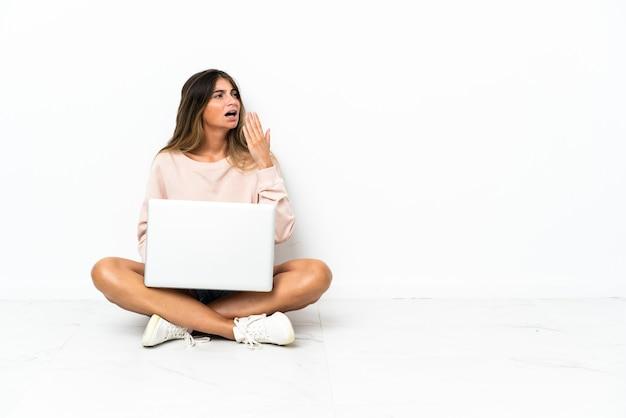 Młoda kobieta z laptopem siedząc na podłodze na białym tle