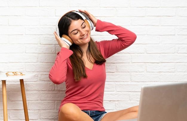Młoda kobieta z laptopem siedząc na podłodze