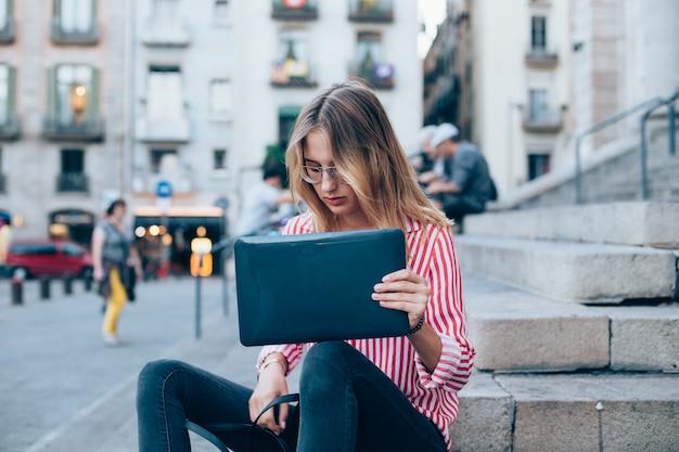Młoda kobieta z laptopem siedząca na schodach, niedaleko uniwersytetu