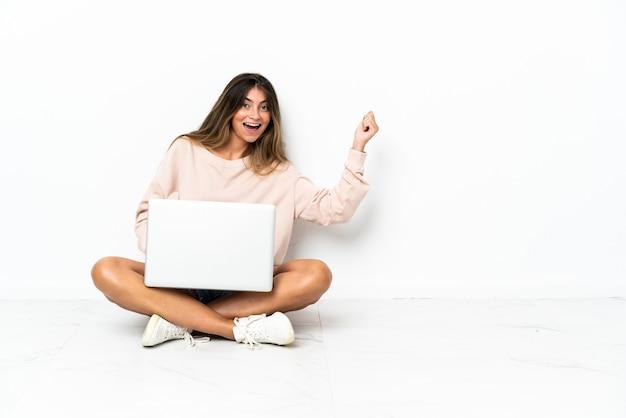 Młoda kobieta z laptopem siedzi na podłodze na białym tle dokonywanie gitara gestu