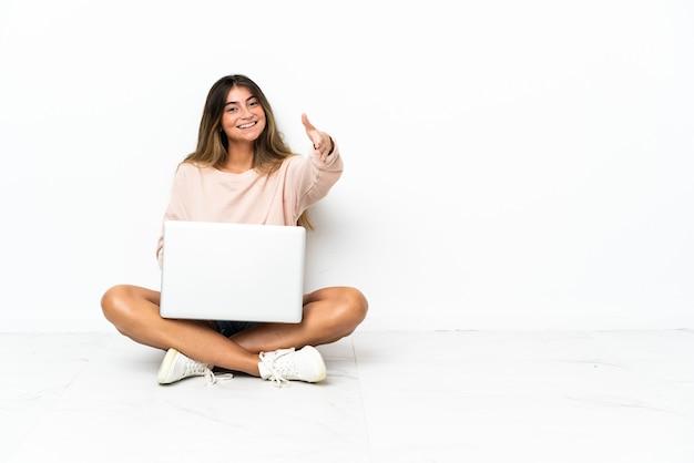 Młoda kobieta z laptopem siedzi na podłodze na białym tle, ściskając ręce, aby zamknąć dobrą ofertę