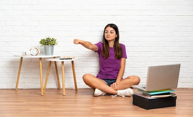 Młoda kobieta z laptopem siedzi na podłodze w pomieszczeniu, dając kciuk do góry gest