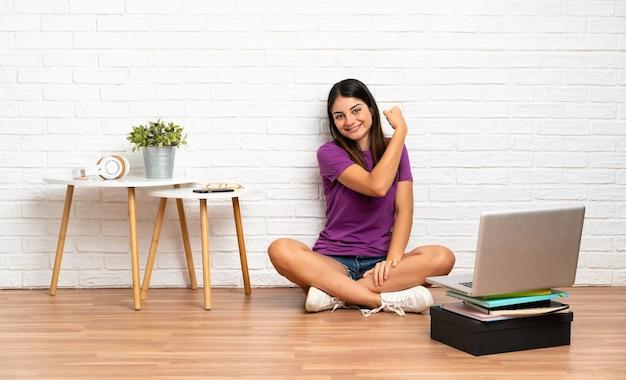 Młoda kobieta z laptopem siedzi na podłodze w pomieszczeniu, robi silny gest