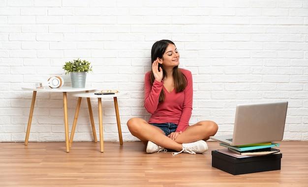 Młoda kobieta z laptopem siedzi na podłodze w pomieszczeniu, słuchając czegoś, kładąc rękę na uchu