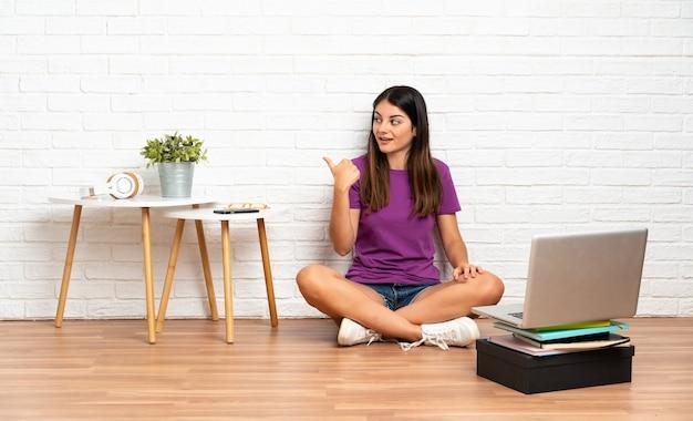 Młoda kobieta z laptopem siedzi na podłodze w pomieszczeniu z zamiarem rozwiązania problemu podnosząc palec do góry