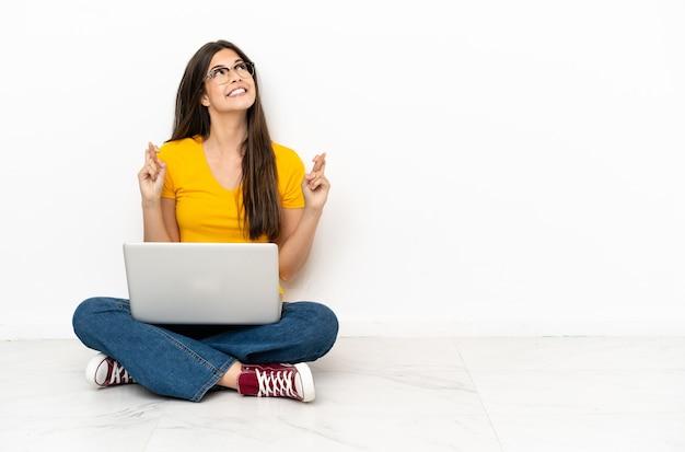 Młoda kobieta z laptopem siedzi na podłodze ze skrzyżowanymi palcami