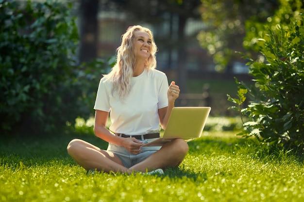 Młoda kobieta z laptopem siedzi na trawie w parku w słoneczny dzień.