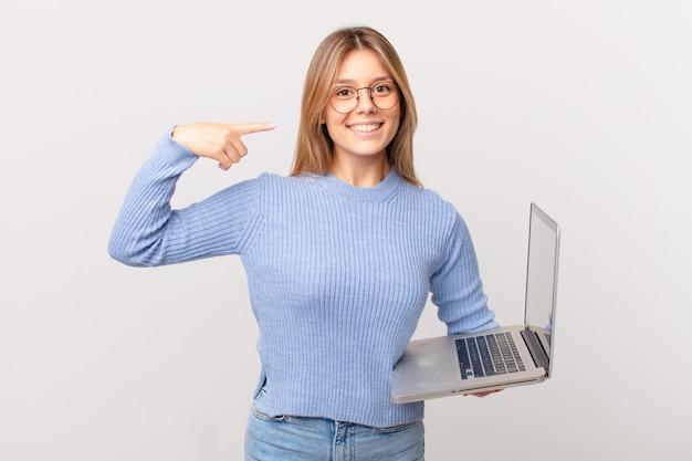 Młoda kobieta z laptopem uśmiecha się pewnie wskazując na swój szeroki uśmiech
