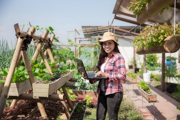 Młoda kobieta z laptopem w gospodarstwie rolnym
