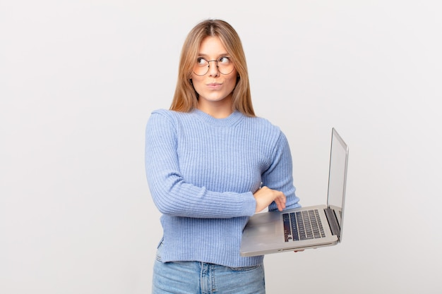Młoda kobieta z laptopem wzrusza ramionami, czuje się zdezorientowana i niepewna
