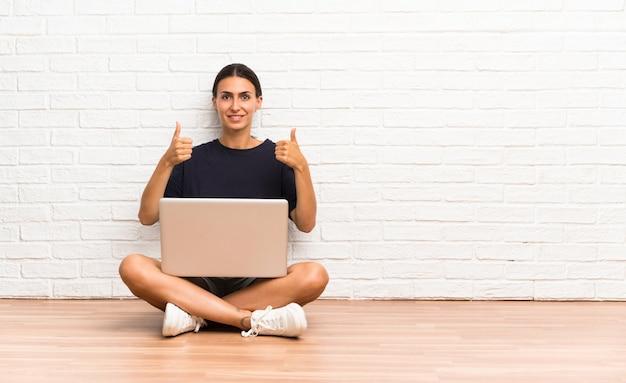 Młoda kobieta z laptopu obsiadaniem na podłoga daje aprobata gestowi