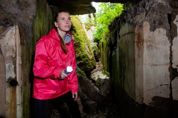 Młoda kobieta z latarnią, ubrana w czerwony płaszcz wodny, bada starożytną jaskinię fortecą