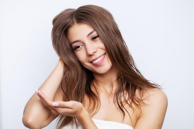 Młoda kobieta z luksusowymi włosami stosuje odżywkę do pielęgnacji włosów