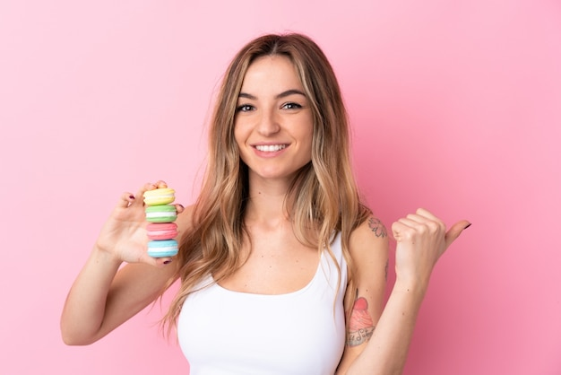 Młoda kobieta z macarons na pojedyncze różowe ściany, wskazując na bok, aby przedstawić produkt