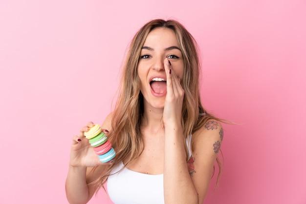 Młoda kobieta z macarons nad odosobnioną menchii ścianą krzyczy z usta szeroko otwarty