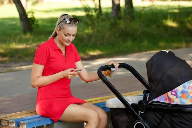 Młoda kobieta z mądrze telefonem i spacerowiczem w parku