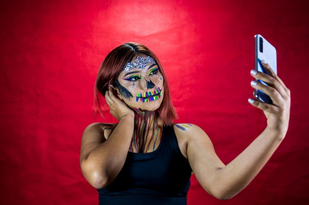 Młoda kobieta z makijażem na imprezę z okazji halloween robi sobie selfie ze swojego telefonu komórkowego