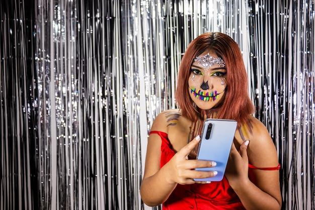 Młoda kobieta z makijażem na przyjęcie z okazji halloween jasne czarno-białe tło telefon komórkowy w ręku
