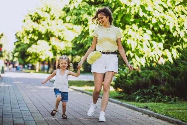 Młoda kobieta z małym córki odprowadzeniem w parku