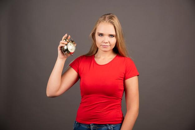 Młoda kobieta z małym zegarem stojącym na czarnej ścianie.