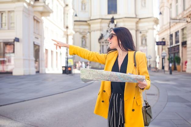 Młoda kobieta z mapą miasta w mieście. podróżuj turystyczną dziewczynę z mapą w wiedniu na zewnątrz podczas wakacji w europie.