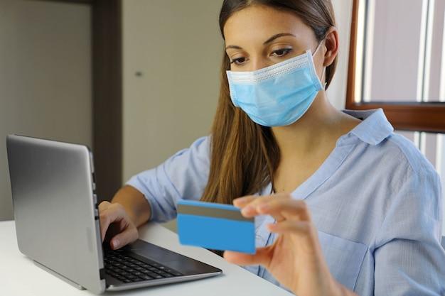 Młoda kobieta z maską kupuje online za pomocą karty kredytowej podczas domowej kwarantanny na chorobę wirusową 2019-ncov.