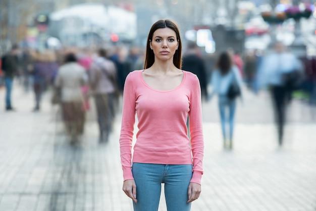 Młoda kobieta z maską medyczną na twarzy stoi pośrodku ludzkiego przepływu
