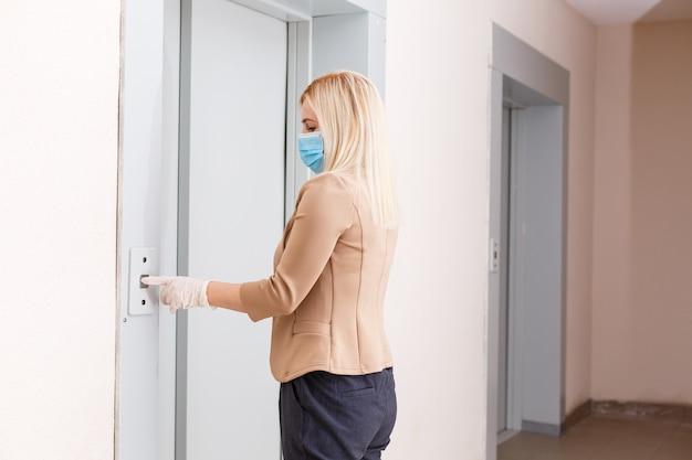 Młoda kobieta z maską medyczną w windzie budynku mieszkalnego