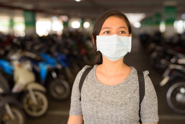 Młoda kobieta z maską myśli na parkingu