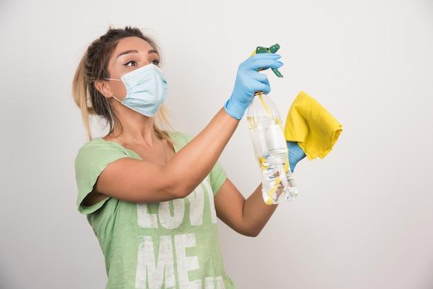 Młoda kobieta z maską na twarz i dostawami rozpylanie na białej ścianie.
