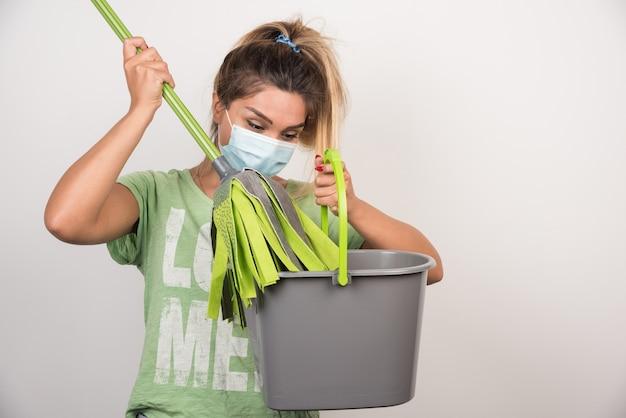 Młoda kobieta z maską na twarzy patrząc na mopa na białej ścianie.