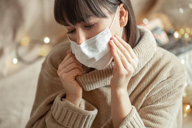 Młoda kobieta z maską na twarzy w przytulnym beżowym swetrze