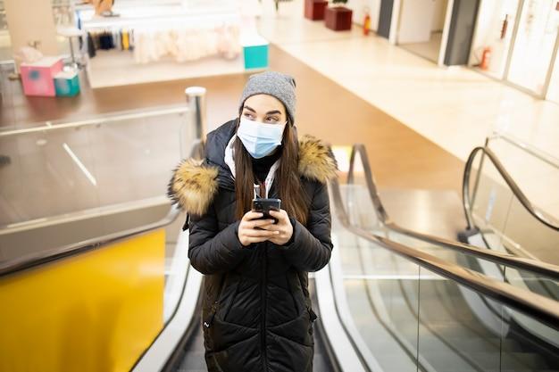 Młoda kobieta z maską ochronną po schodach w centrum handlowym