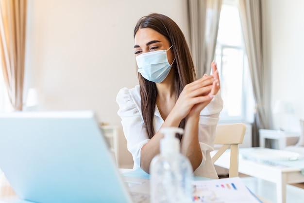 Młoda kobieta z maską ochronną, pracująca w domu