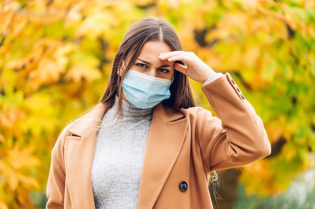 Młoda kobieta z maską ochronną w jesiennym parku
