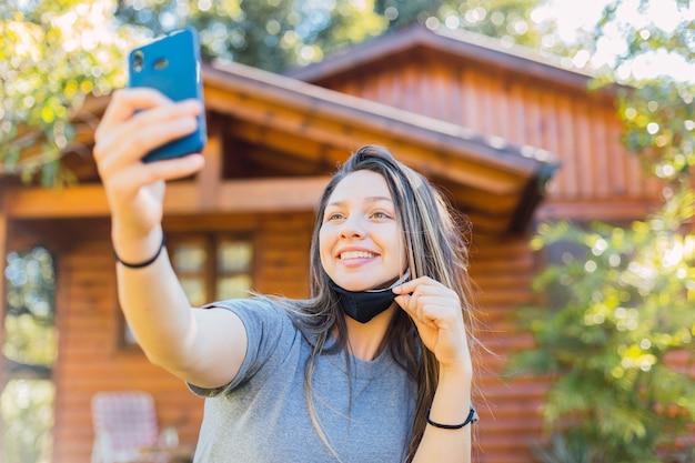 Młoda kobieta z maską przy selfie