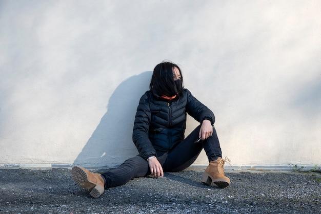 Młoda kobieta z maską siedzi na podłodze na zewnątrz
