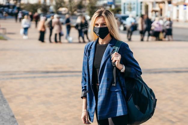 Młoda kobieta z maską spaceru w mieście