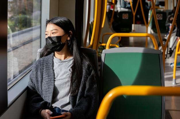 Młoda kobieta z maską w autobusie